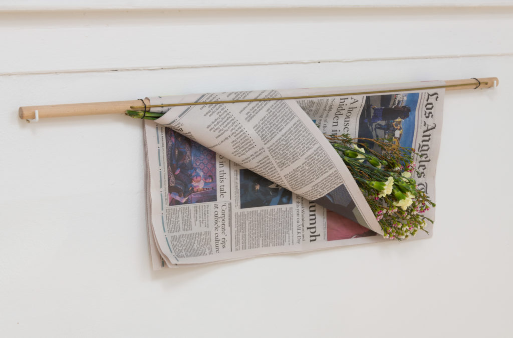Brian Khek, Wednesday Newspaper Stick, 2016. Newspaper, flowers, poplar, and brass rod. 36 x 2 x 12 inches. Courtesy the artist and Garden, Los Angeles. Photo: Jeff McLane.